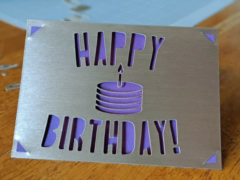 Silver and purple card with Happy Birthday and a small cake cut out of the front.