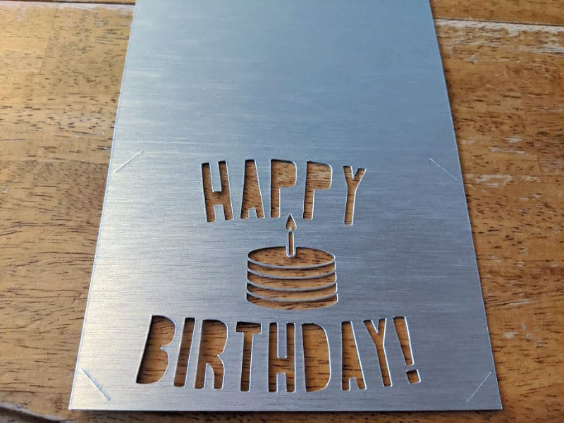 Thick shiny silver paper with the words happy birthday cut out.
