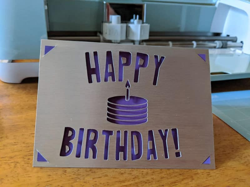 Completed silver and purple birthday card standing on table in front of Cricut machine.