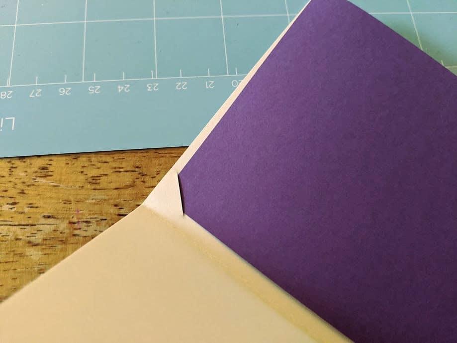 Adding purple cardstock insert into DIY birthday card.