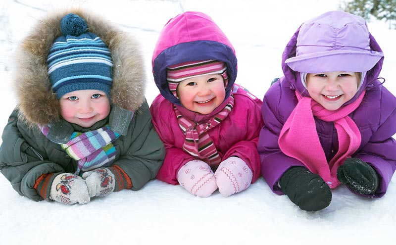 Three little kids laying on the snow and wearing outdoor winter gear.