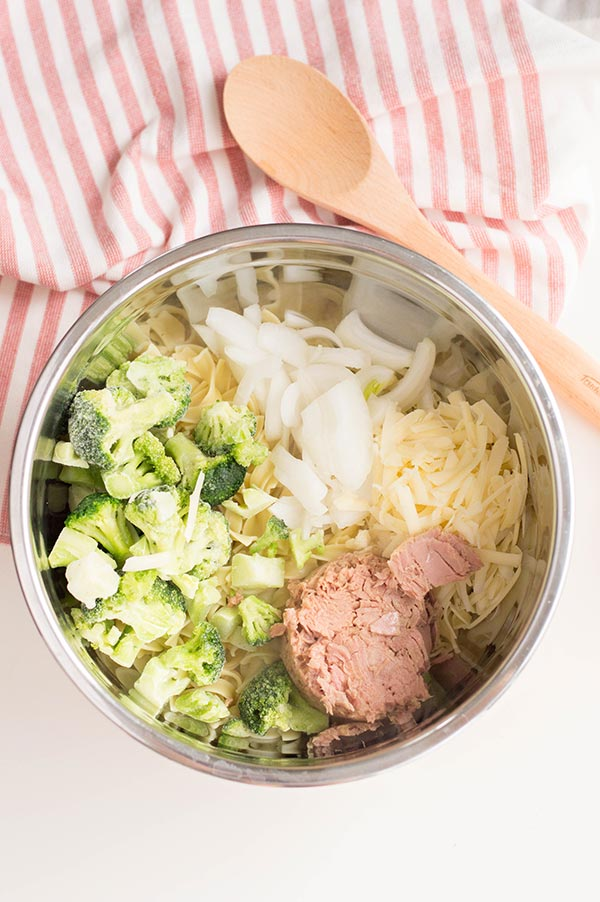 Broccoli, onion, shredded cheese, canned tuna fish in silver bowl next to wood spoon on red and white kitchen cloth.