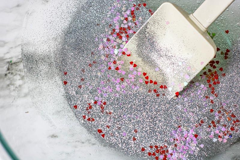 White spatula mixing silver glitter, red foil heart confetti, and pink foil heart confetti into glue mixture.