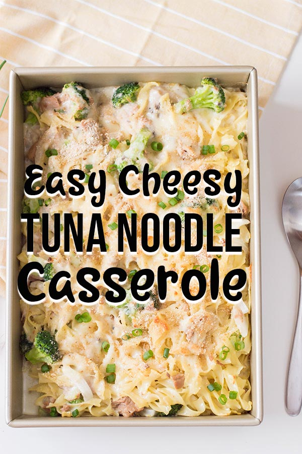 Overhead view of full baking pan with cheesy tuna noodle casserole with serving spoon laying next to it and light yellow cloth. Text overlay with recipe name.