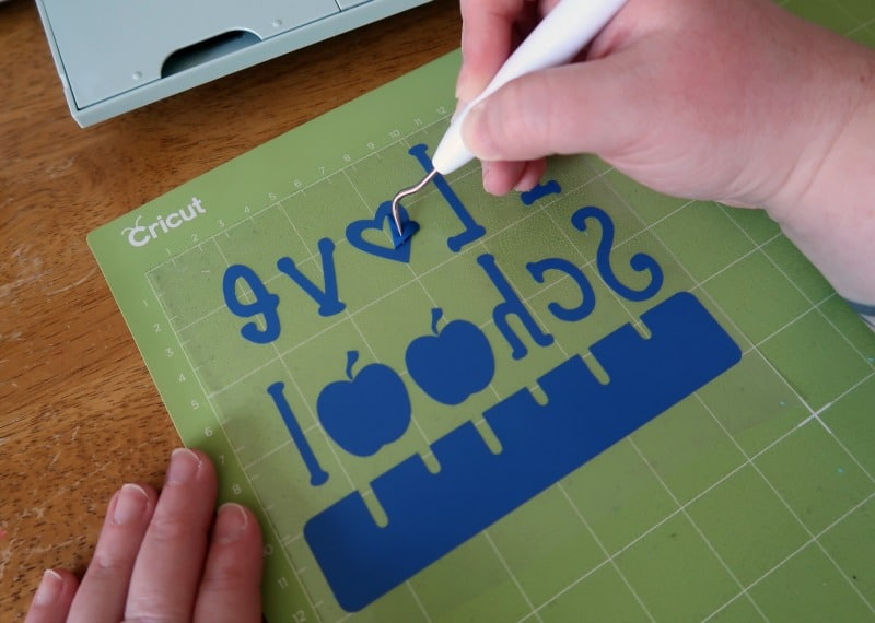 Using weeding tool to remove small pieces of iron on vinyl from design cut by Cricut machine.