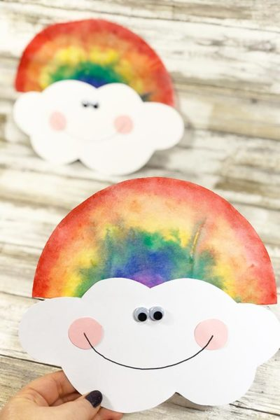 Woman's hand holding finished rainbow colored coffee filter with cute smiling cloud face. Another completed project is laying down in the background.