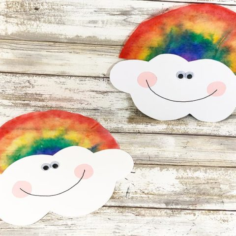 Two coffee filter rainbows with smiling clouds laying on white wood photo background.
