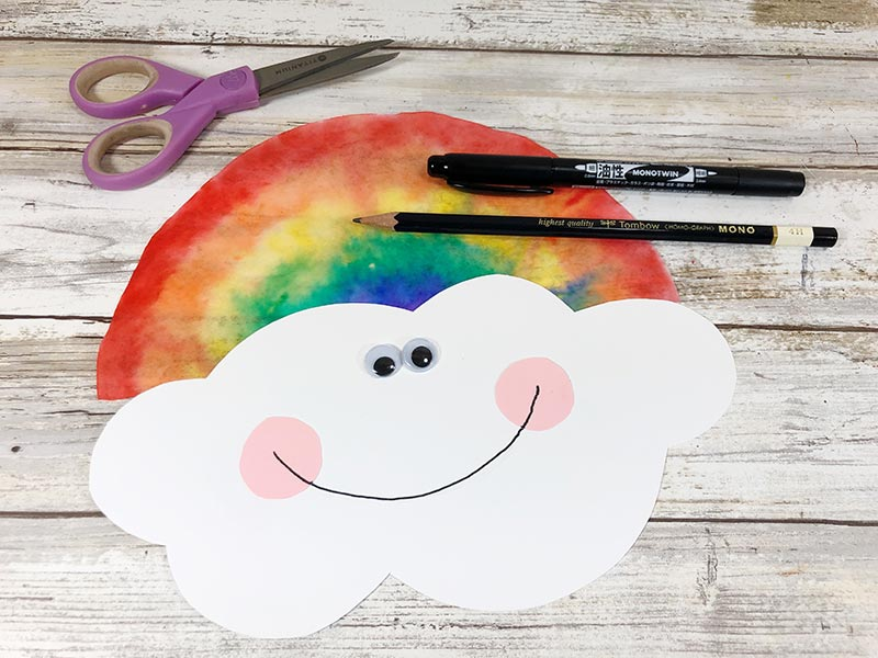 White cloud shape glued to rainbow coffee filter. Googly eyes and cute smile added to cloud to make a face.