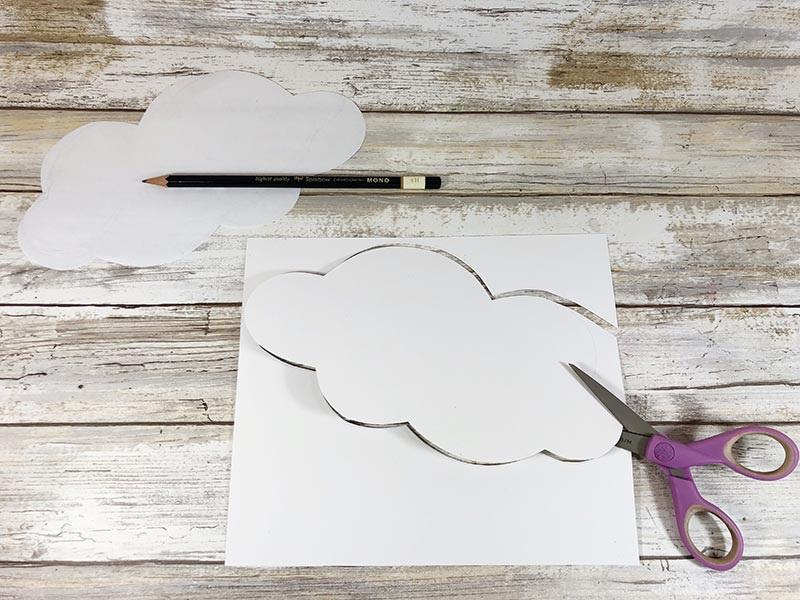 One paper cloud cut out of white paper and another traced and getting cut out.