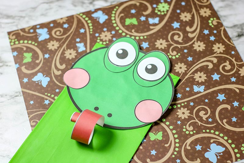 Closer view of paper bag frog puppet using paper cut outs for face and green bag.