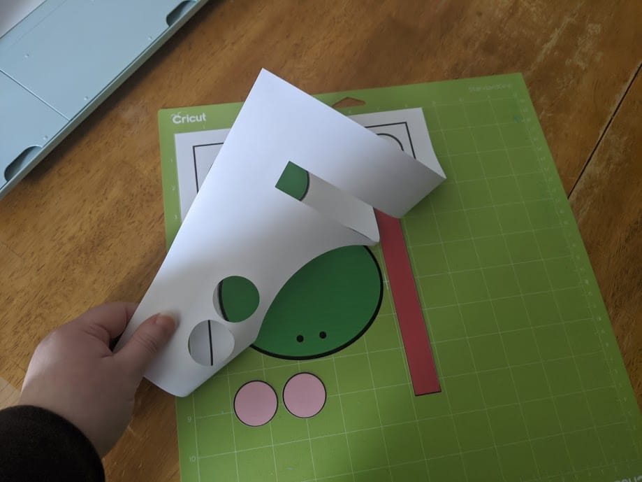 Pulling white cardstock off Cricut mat leaving frog craft pieces.