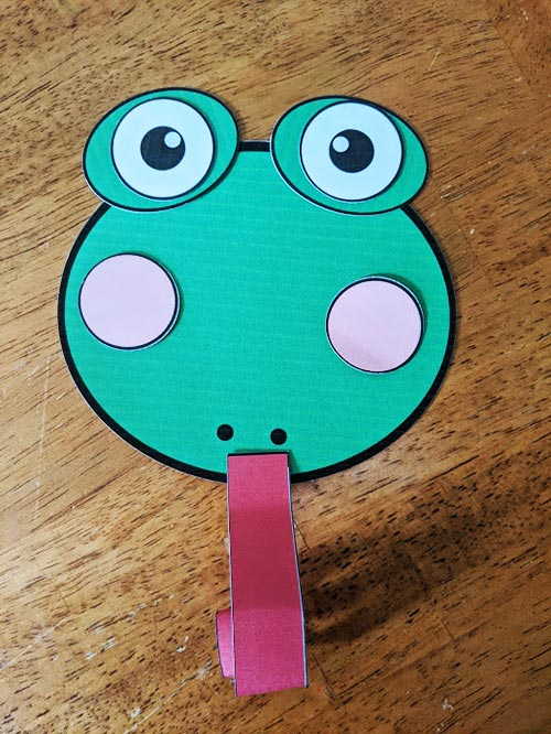 Paper cut outs for making frog face craft with curled tongue.