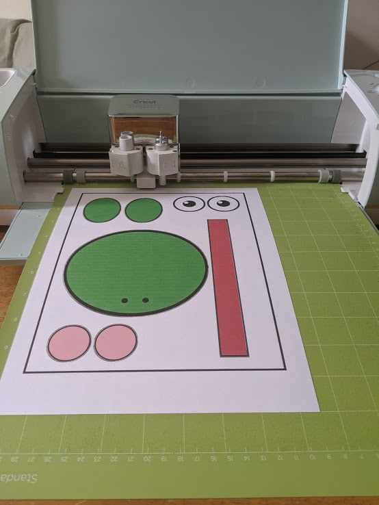 Frog template printed on cardstock and on mat in Cricut cutting machine.