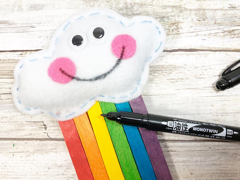 Close up of stuffed felt cloud with googly eyes, pink cheeks, and hand drawn smile.