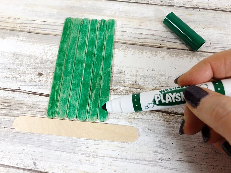 Coloring popsicle sticks with green marker.