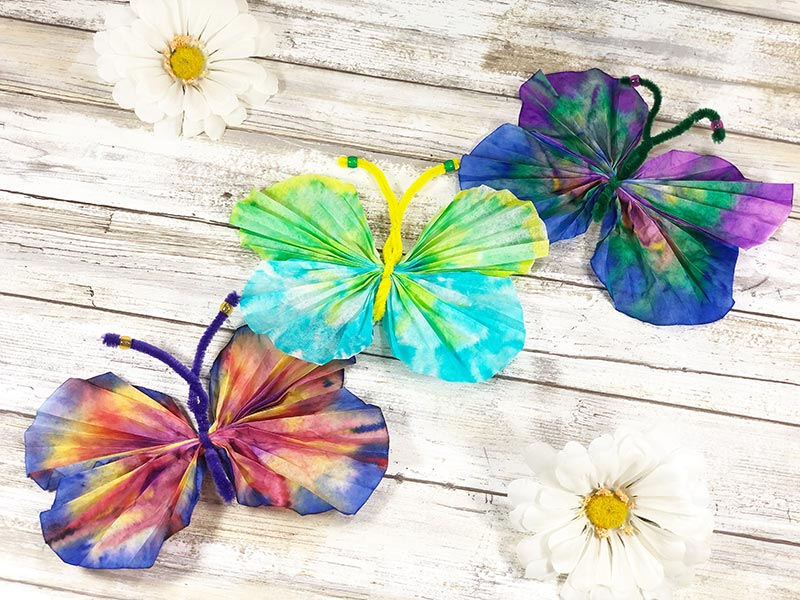 Three coffee filter butterflies in different colors laying next to each other.