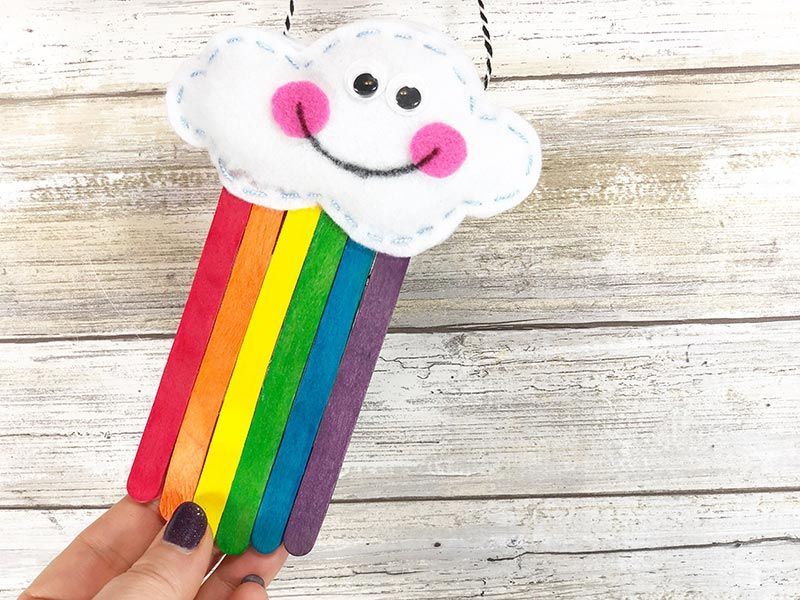 Hand holding up completed rainbow popsicle stick craft.