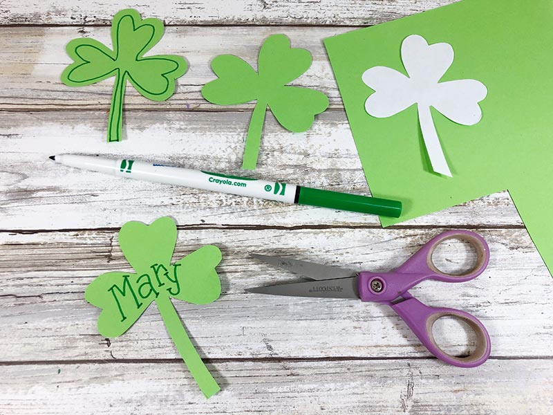 Shamrock cutouts and template laying on green paper. One shamrock says Mary.