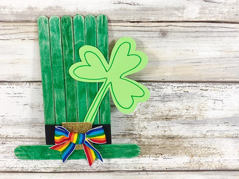 Overhead view of green top hat made with popsicle sticks and decorated with a paper shamrock.
