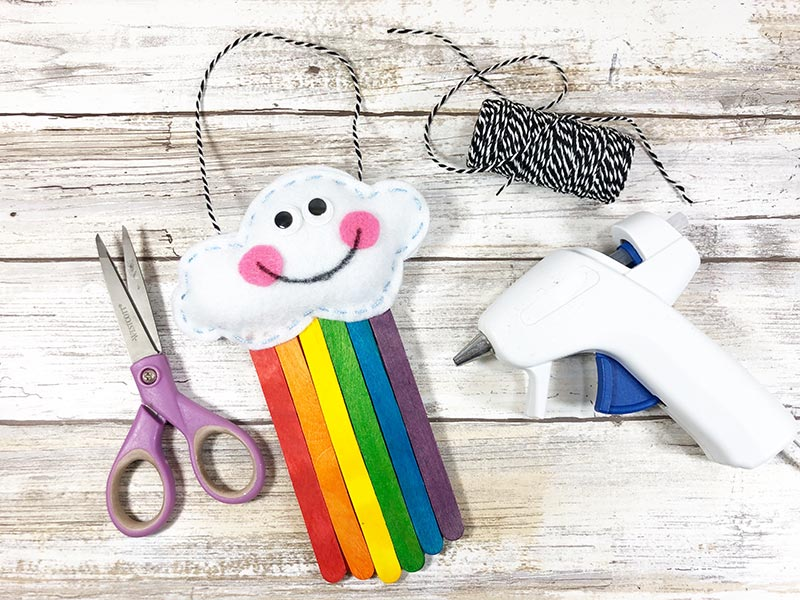 Completed cloud and rainbow craft decoration laying next to scissors, twine, and glue gun.