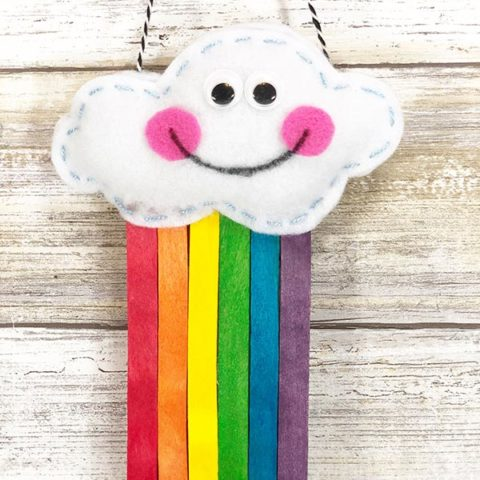 Stuffed cloud with smiley face and rainbow colored popsicle sticks coming out the bottom is hanging up.