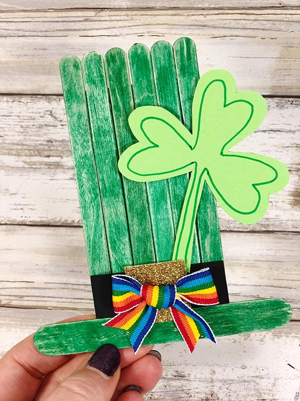 Hand holding completed green leprechaun hat made from popsicle sticks.