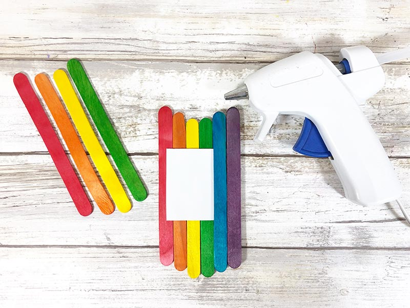 Popsicle sticks arranged in rainbow color order next to glue gun.