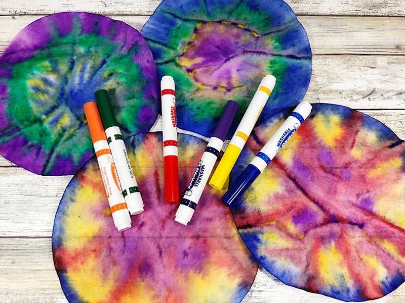 Four coffee filters tie dyed with markers.