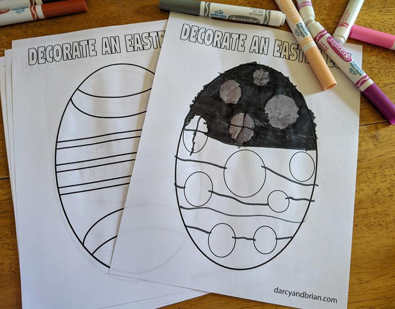Printed Easter egg coloring sheets on table by markers. One egg is partially colored in.