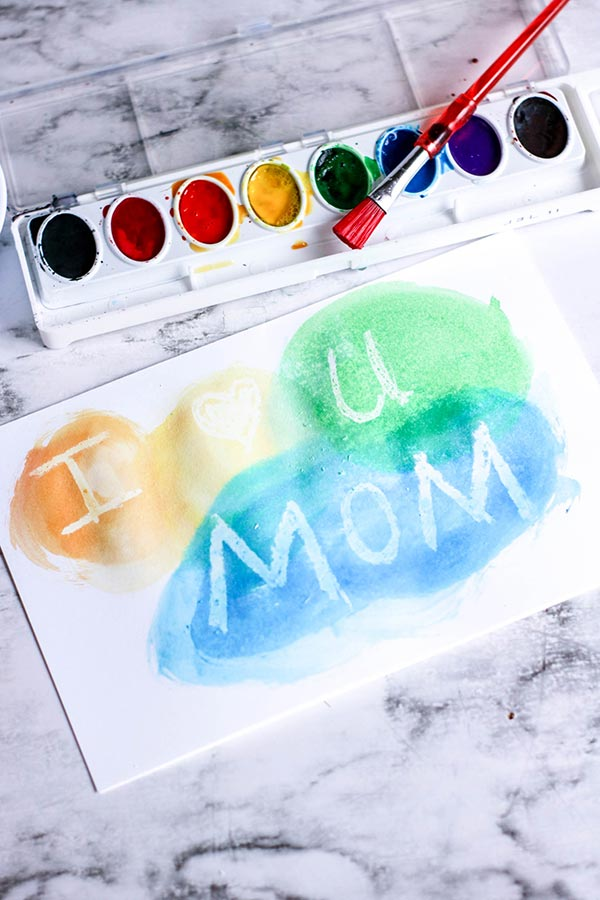 Painting with watercolors over white crayon reveals message or design.