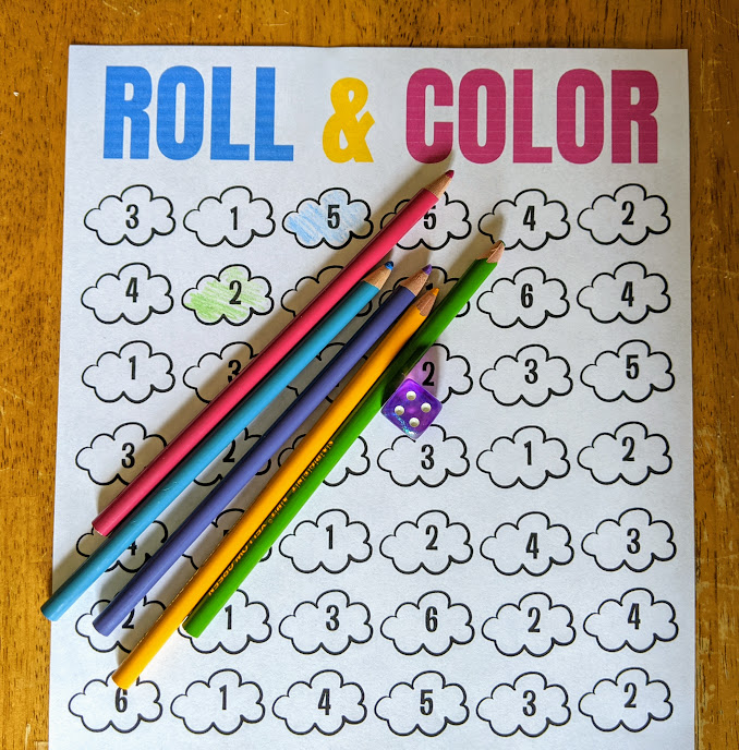 Cloud roll and color math game printed out and set on wooden table with colored pencils and six sided die.