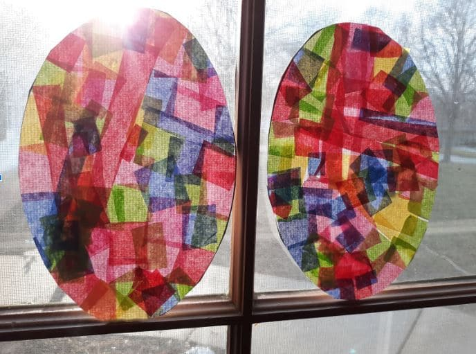 Two finished tissue paper Easter egg suncatchers hanging in sunny window.