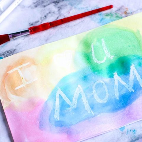 Finished watercolor resist Mother's Day card with multiple colors painted on front. Message says I heart U Mom