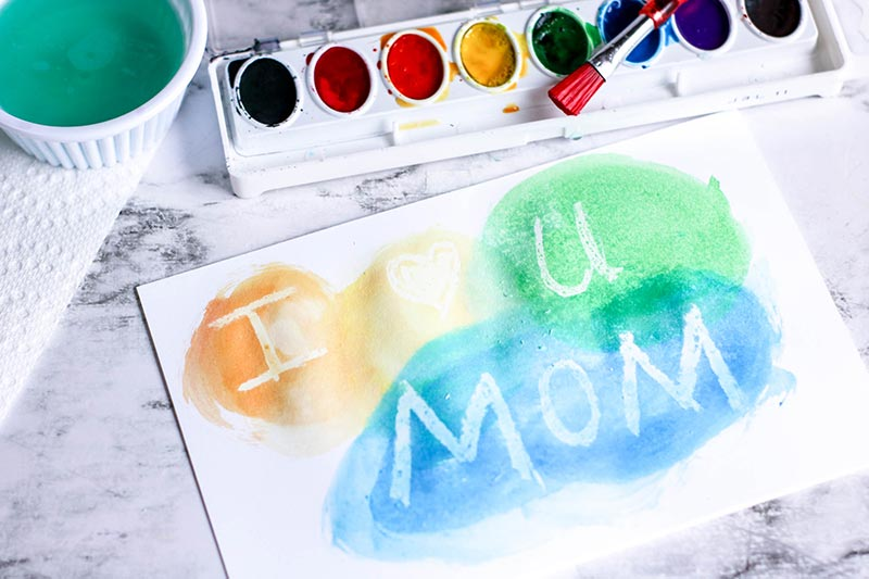 Yellow, green, and blue watercolor paints on card revealing I heart you Mom.