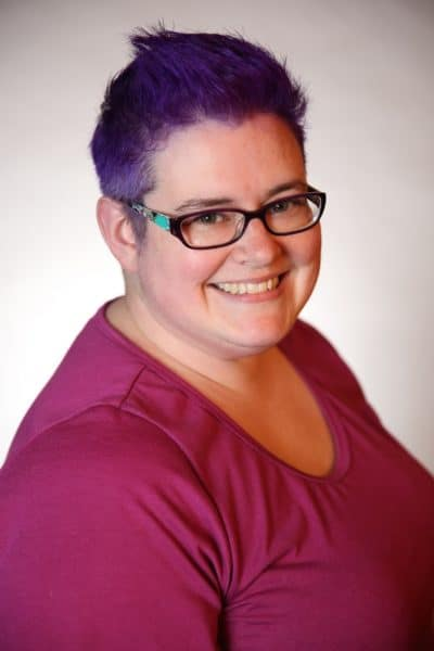 Headshot photo of white woman with short purple hair, glasses, smiling, wearing a dark pink top.
