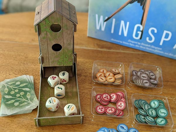 Bird feeder dice tower on table next to food tokens and Wingspan game box.