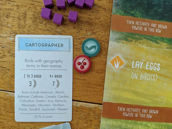 Cartographer bonus card laying on table next to player mat, food tokens, and purple wooden cubes.