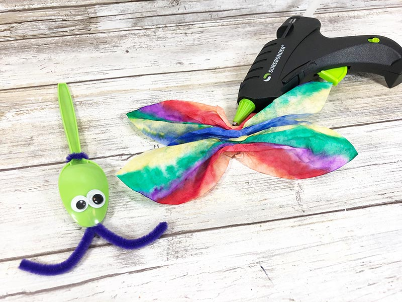 Green plastic spoon with googly eyes and purple chenille stem antenna laying on white wood background next to rainbow colored coffee filter wings and glue gun.