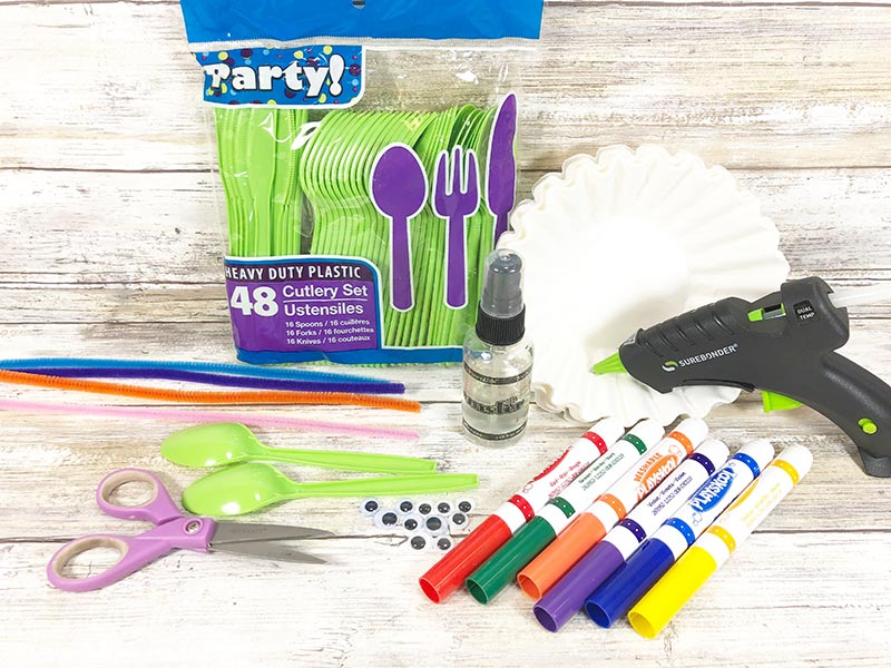 Pack of green plastic spoons, coffee filters, pipe cleaners, googly eyes, markers, scissors, and hot glue gun on white wood background.