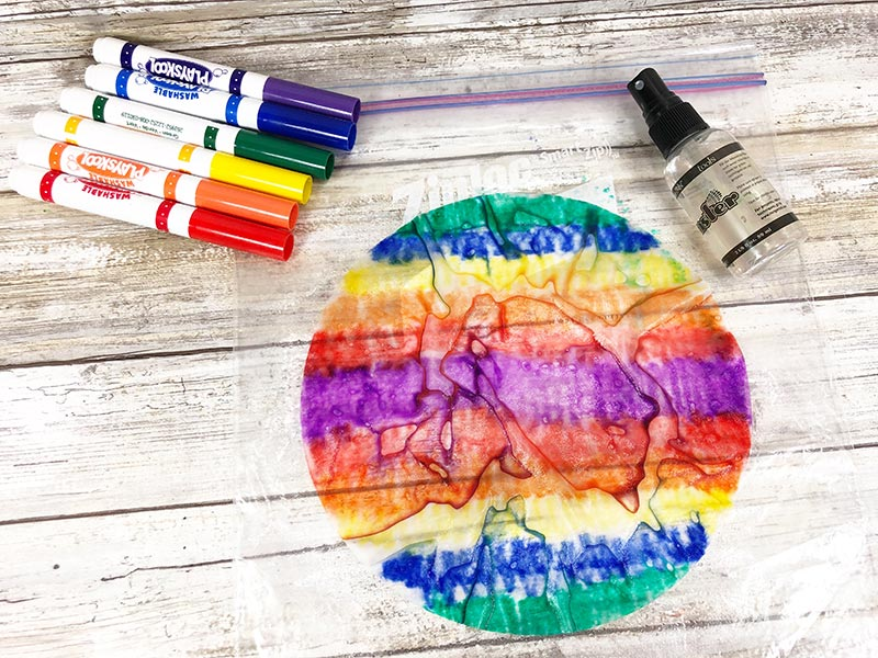 Wet colored coffee filter with colors blending, washable markers, and small water spray bottle laying on white wood background.