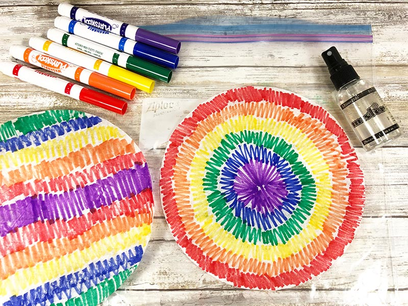 Two rainbow colored coffee filters and markers laying on white wood background.