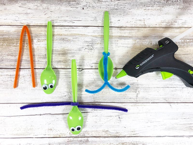 Three green plastic spoons with googly eyes laying next to each other showing steps of how to attach chenille stem to create antenna for dragonfly.