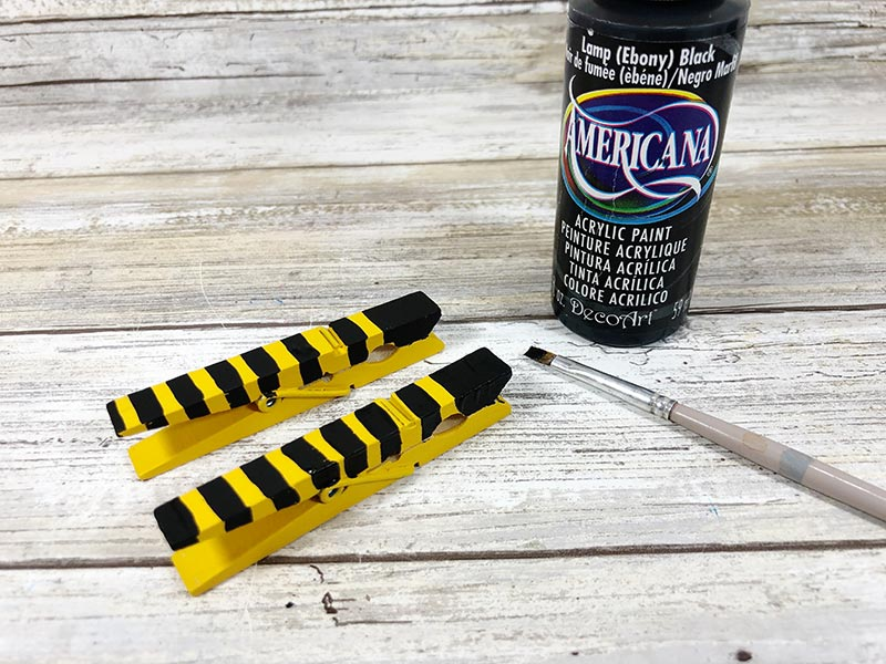 Two clothespins painted yellow with black stripes next to paintbrush and black paint.