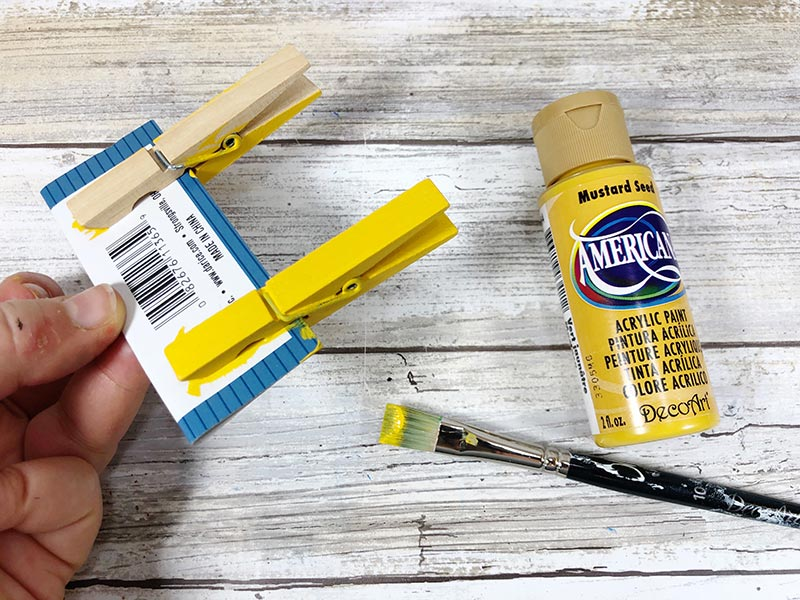 Two wooden clothespins clipped to small piece of cardboard with hand holding the cardboard. One clothespin is painted yellow and the other is unpainted. Paintbrush and yellow paint lay nearby.