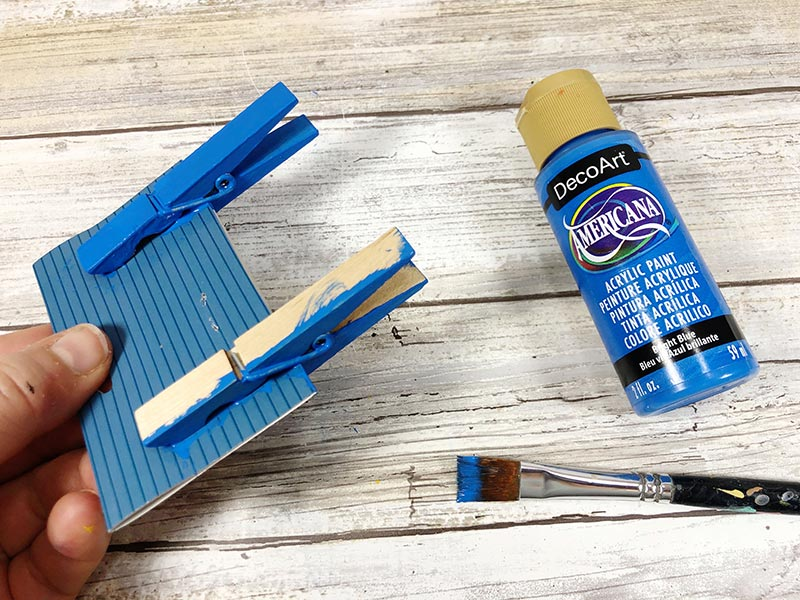 Hand holding piece of cardboard with two wooden clothespins clipped to it. One clothespin is painted blue and the other is in process of being painted. Paint brush and bottle of blue paint laying on white wooden backdrop.