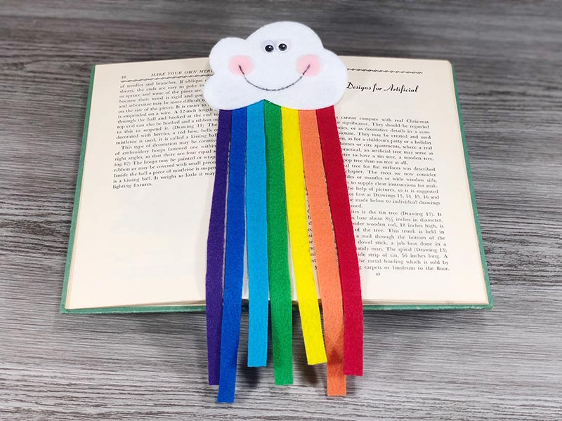 Felt cloud with smiley face and felt rainbow strips coming out of it laying on top of an open book.