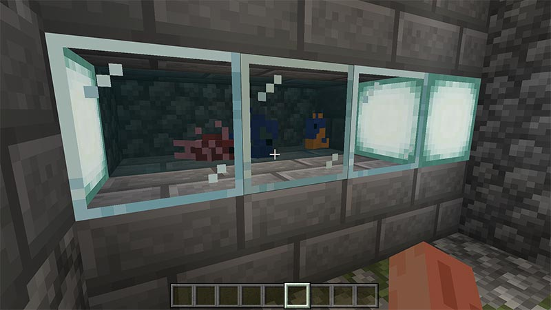 Fish tank built in stone wall using glass blocks in the game Minecraft.