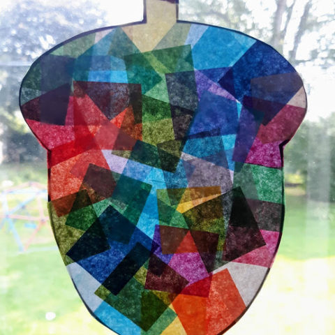 Acorn suncatcher made with tissue paper on window.