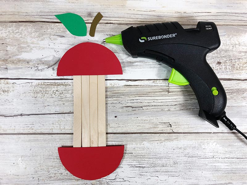 Using glue gun to attach cardstock stem and leaf to top of apple craft.