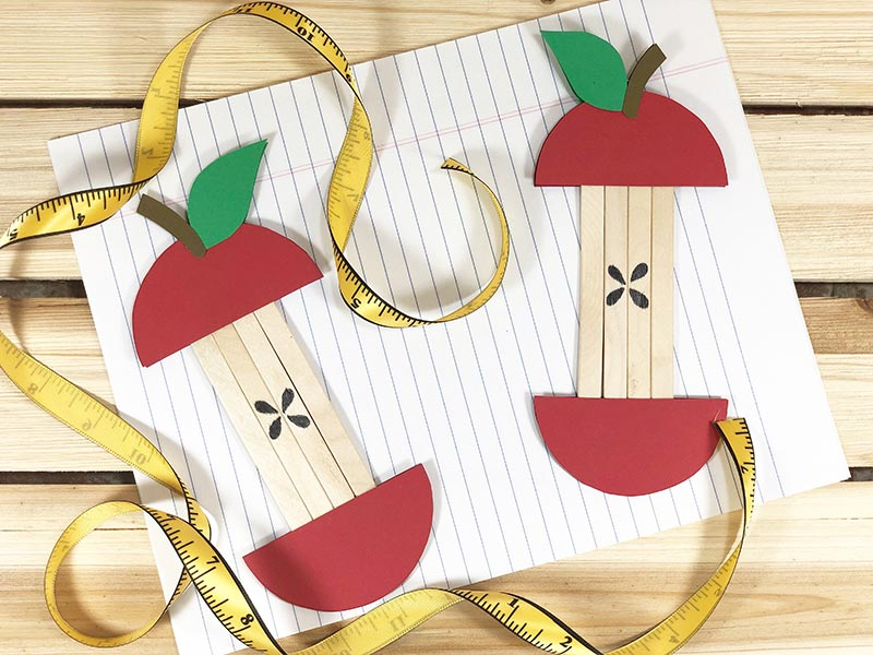 Two popsicle stick apple crafts completely assembled next to soft yellow measuring tape and laying on lined paper.